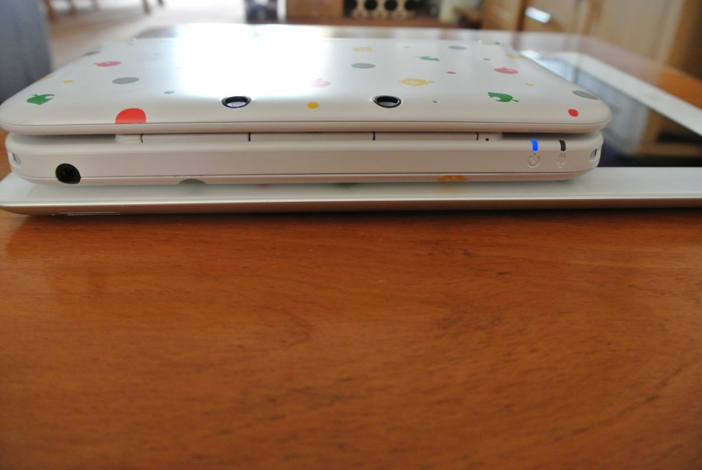 Nintendo 3DS XL On Top Of Apple iPad 2 - Size Comparison