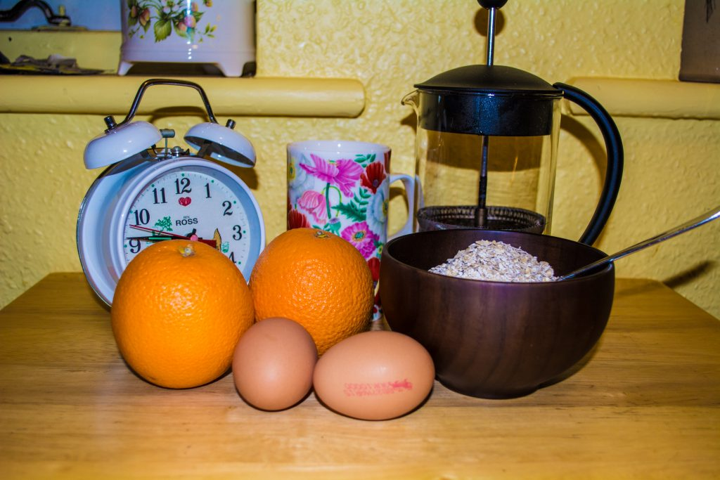 Breakfast; Alarm Clock, Coffee Mug, French Press, Oranges, Eggs, Porridge Oats in Wooden Bowl
