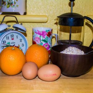 Breakfast; Alarm Clock, Coffee Mug, French Press, Oranges, Eggs, Porridge Oats in Wooden Bowl