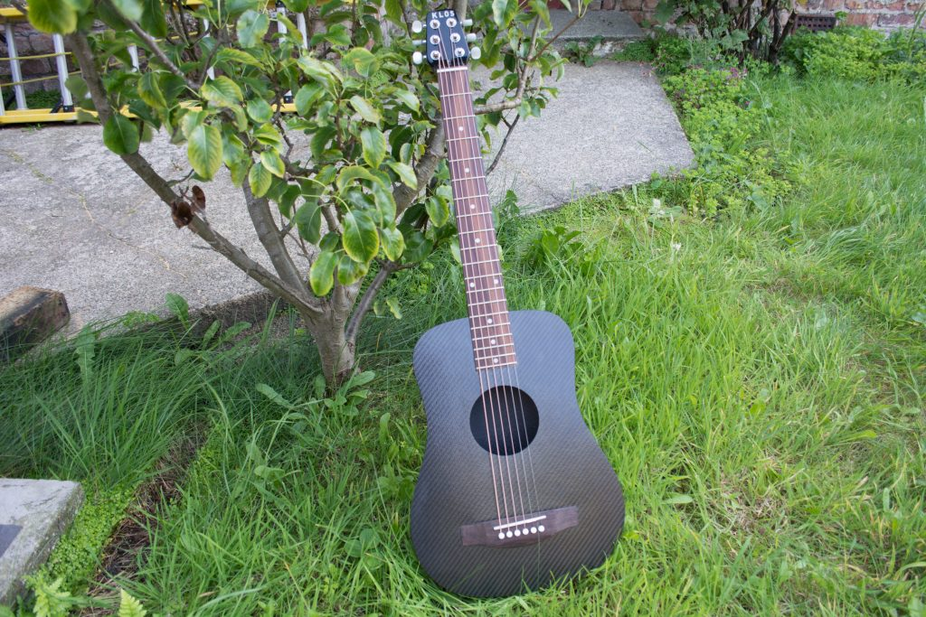 KLŌS 2.0 Carbon Fiber Travel Guitar Leaning Against Tree