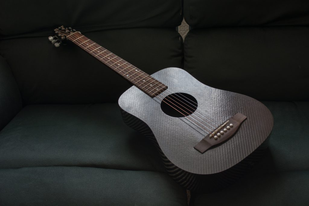 KLŌS 2.0 Carbon Fiber Travel Guitar on Sofa