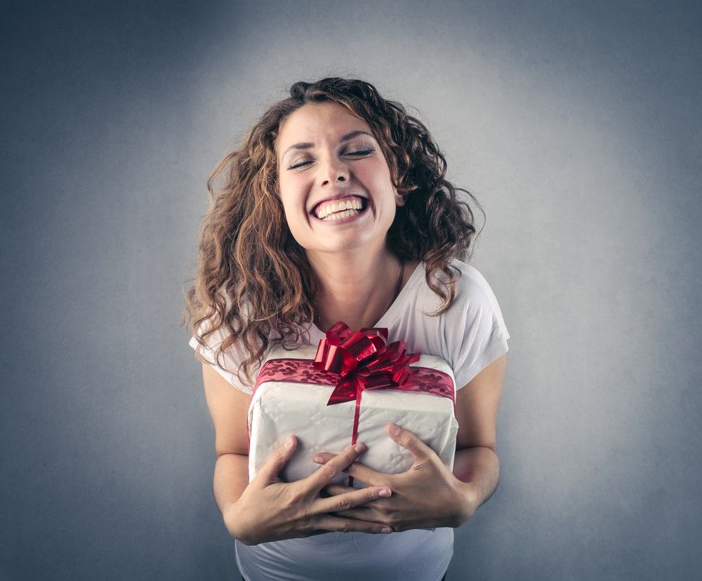 Smiling Woman Holding Present Tied with Red Bow