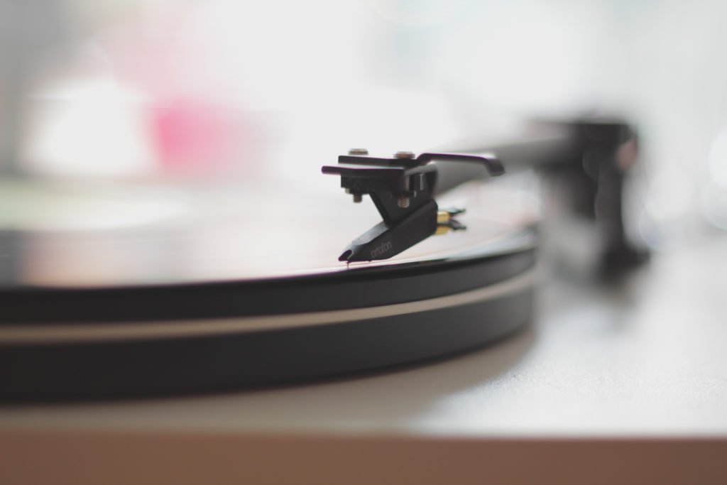 Vinyl record being played on turntable with needle on it