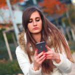 Young Woman Using iPhone Outdoors