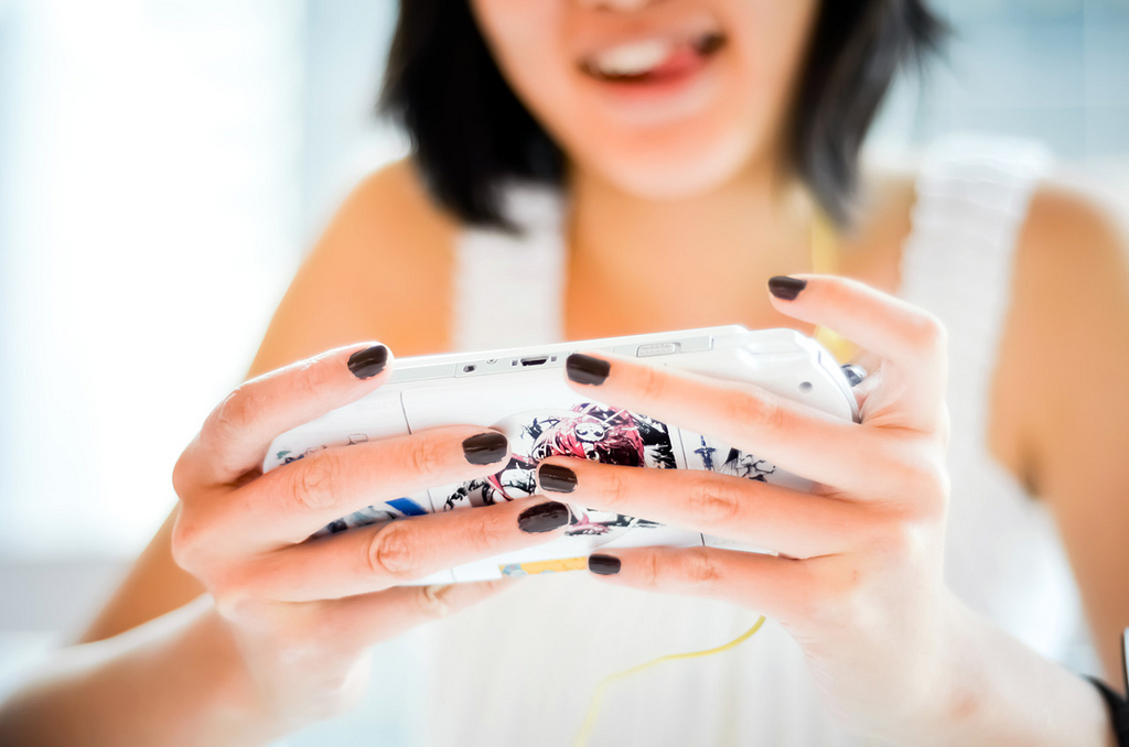 Woman playing a PlayStation Portable (PSP)