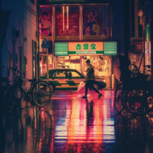 Side view of a woman in an illuminated city at night