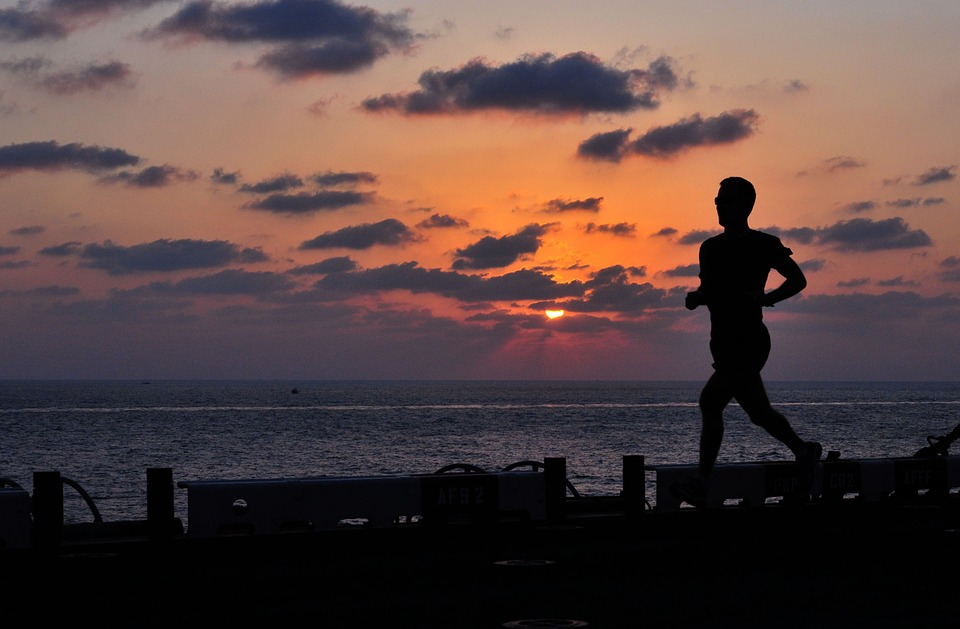 Silhouette of person jogging at sunset