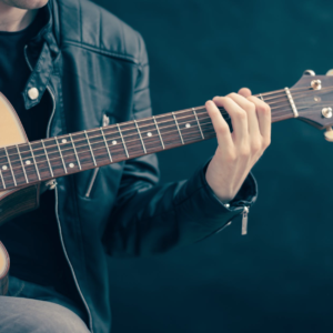 Man in a leather jacket playing acoustic guitar
