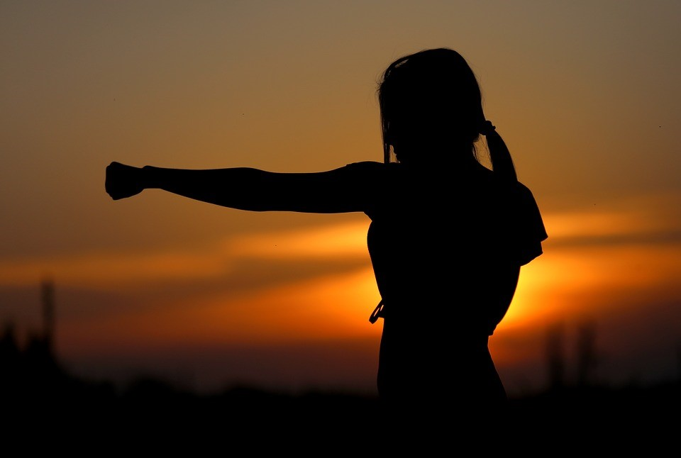 Silhouette of woman training at sunrise