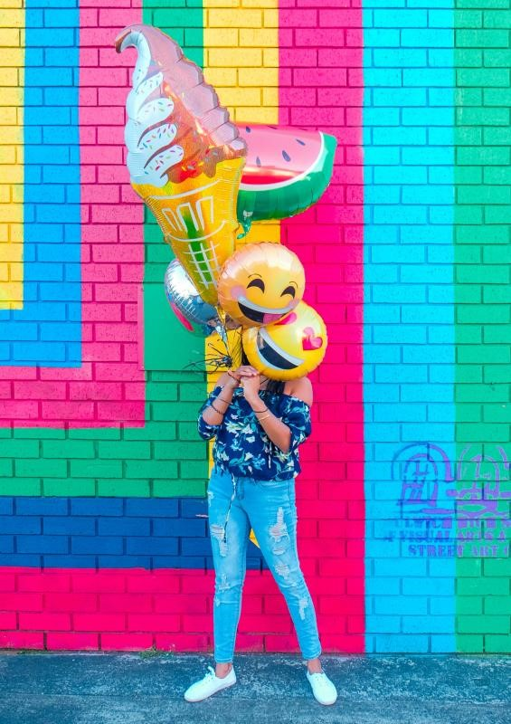 Woman hiding face behind emoji balloons