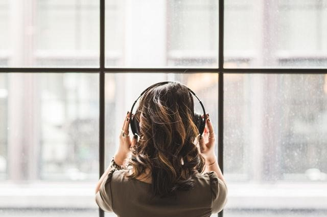 Woman wearing headphones looking out of a window