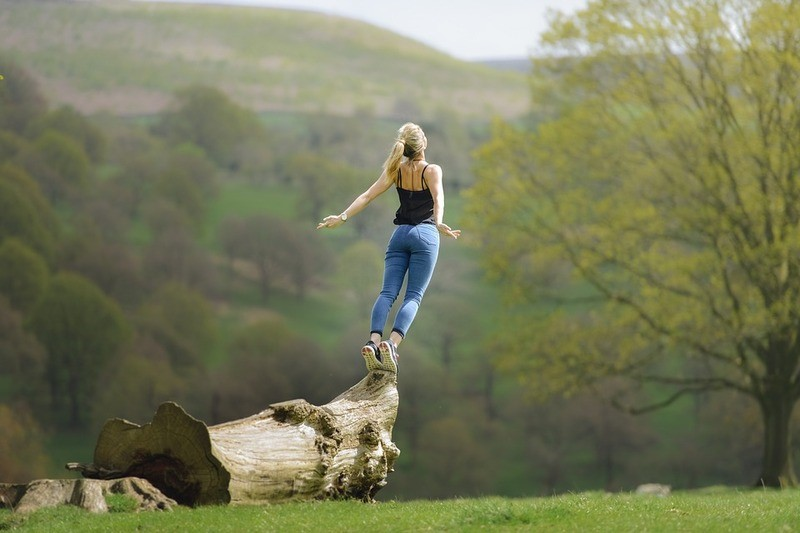 Woman standing on a log outdoors