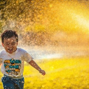 Laughing child running through sprinklers