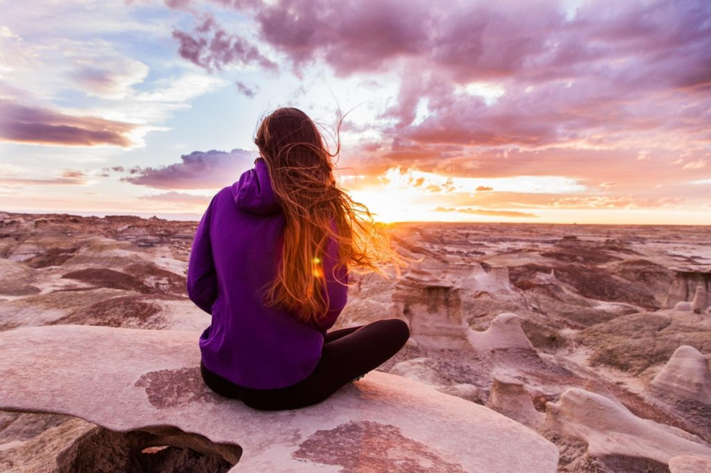 Woman sat on a rock watching the sunset