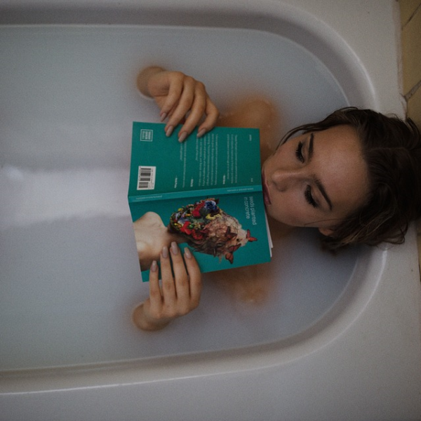 Woman Relaxing By Reading A Book In The Bath