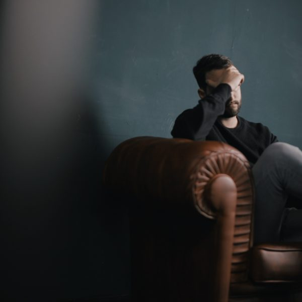 Man with head in his hand on a sofa against a wall
