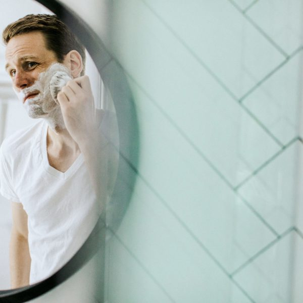 Man applying shaving cream in front of mirror