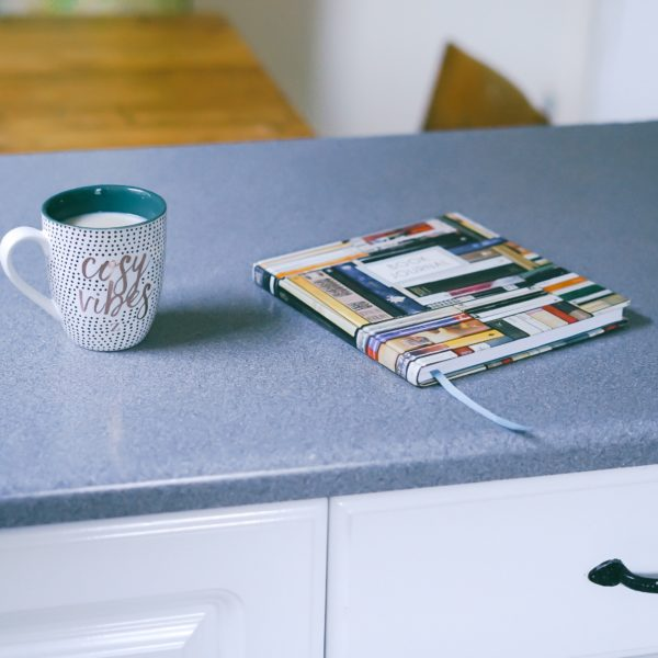 Gray and white ceramic mug beside multicolored covered book