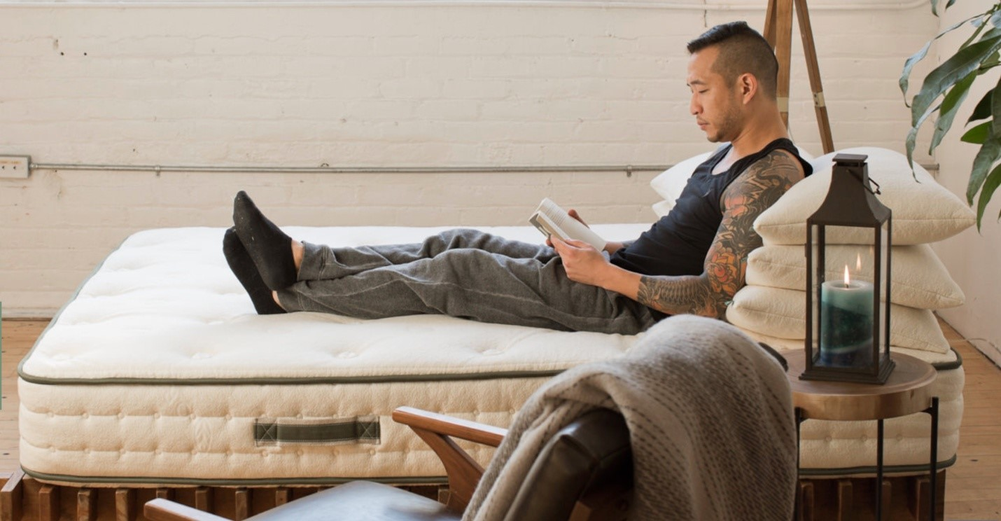 Tattooed man sitting on a bed