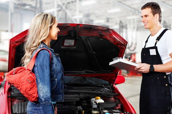 Mechanic talking to woman in front of car