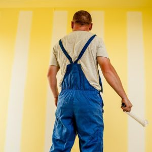 House painter in front of a yellow wall