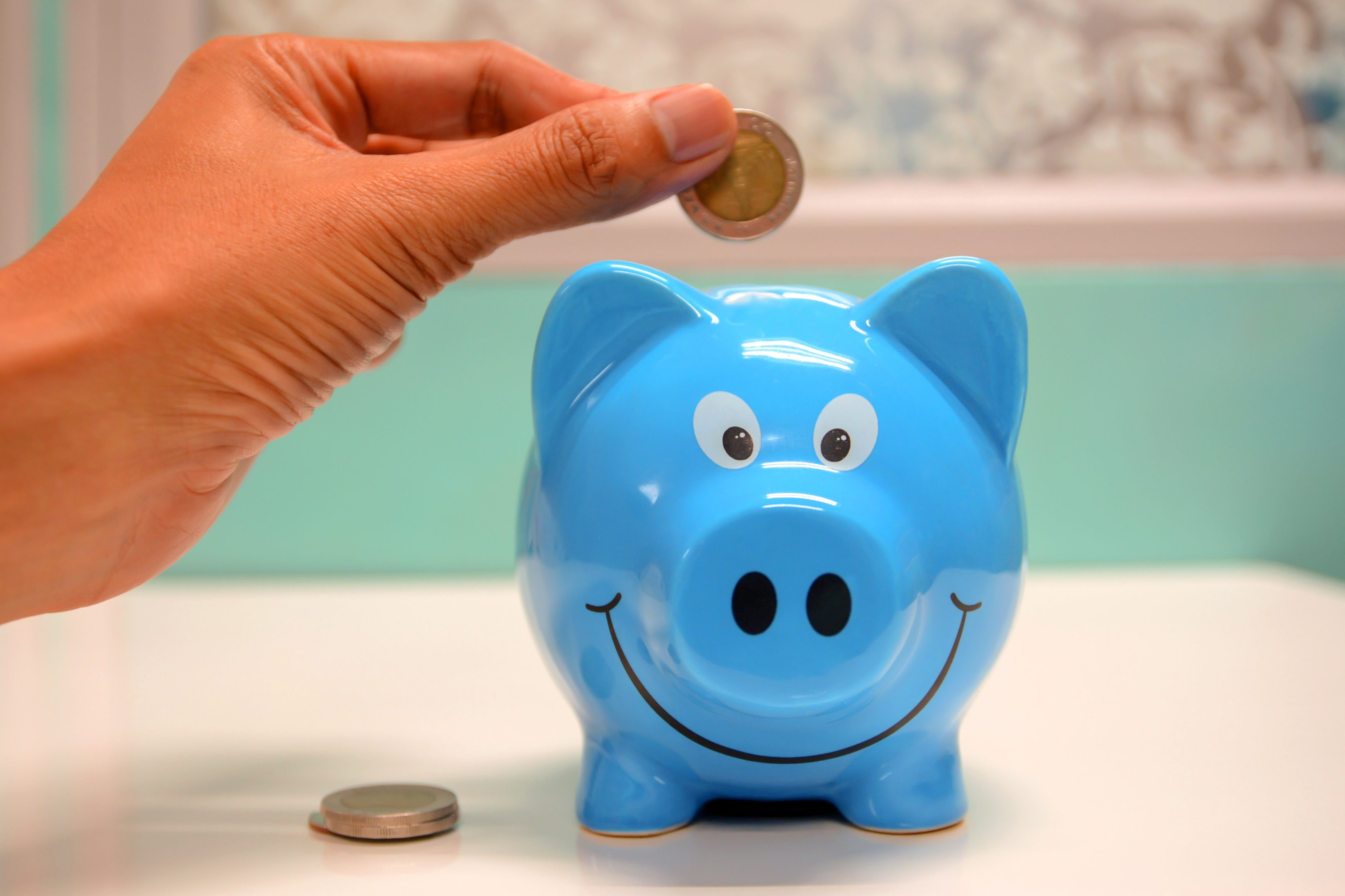 Fingers about to put a coin into a blue piggy bank