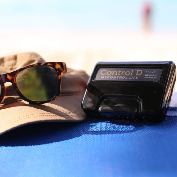 Control D Blood Glucose Monitor on the beach with hat and sunglasses