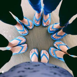 The feet of six people wearing blue flip flops