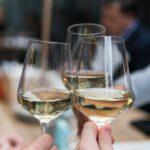 Three people having a toast using three clear crystal wine glasses