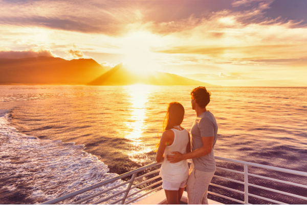 Couple on a boat looking at sunrise