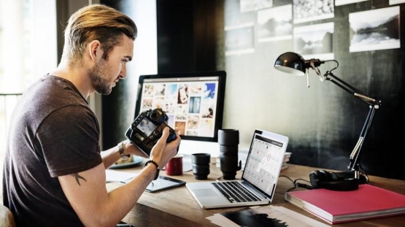 Man holding DSLR at desk