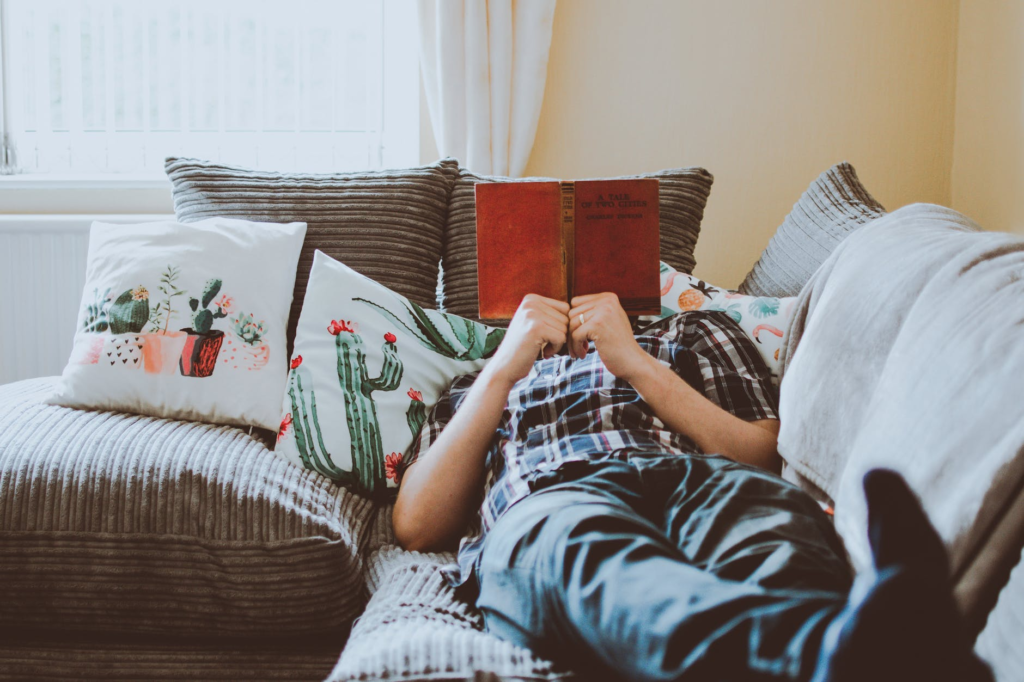 Person lying on couch whilst reading a book