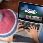 Person playing online poker on laptop
