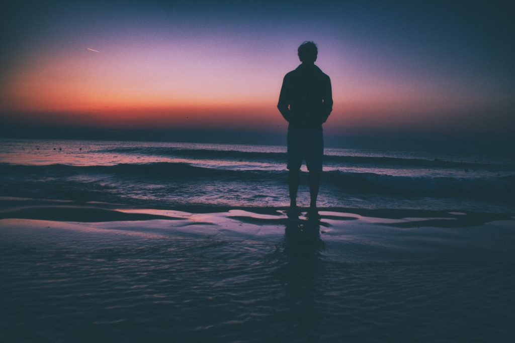 Man standing on beach at sunset
