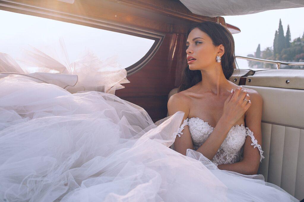 Bride wearing white sweetheart-neckline wedding dress inside vehicle