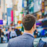 Man wearing blazer in busy city