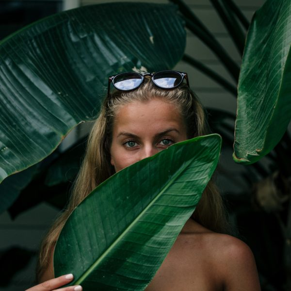 Woman hiding behind leaf