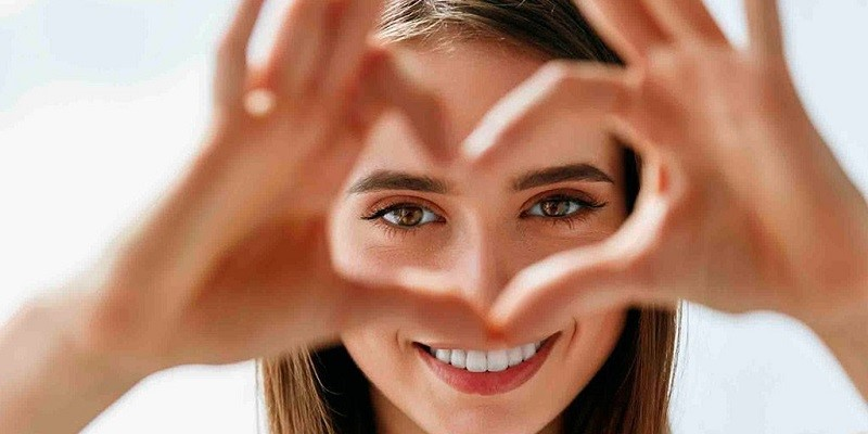 Woman smiling and making a heart with fingers