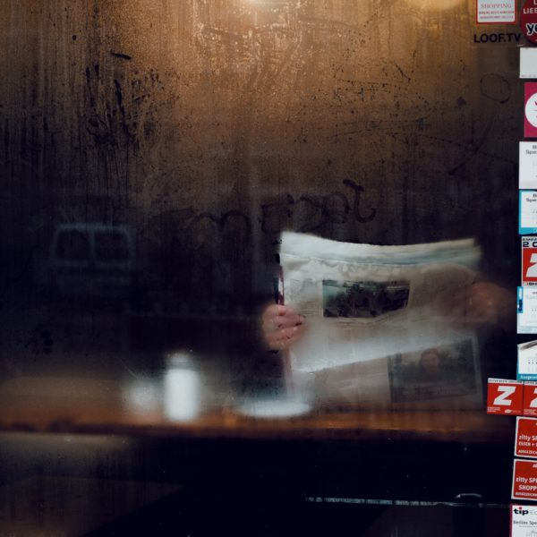Person reading newspaper behind cafe window