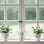 Flowerpots and porcelain teapot on windowsill