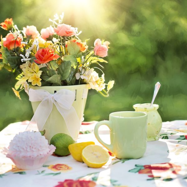 Flowers, food and drink on a table in the sun