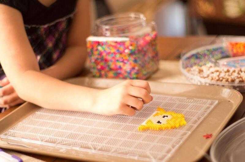 Child creating with beads