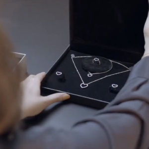 Person looking at a necklace, bracelet, earrings and ring in a jewellery box