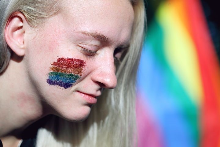 Person with rainbow makeup on cheek