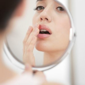 Woman looking at lips in mirror