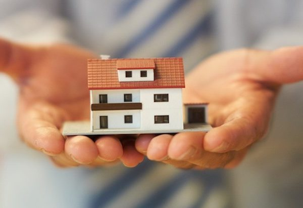 Hands holding a model of a house