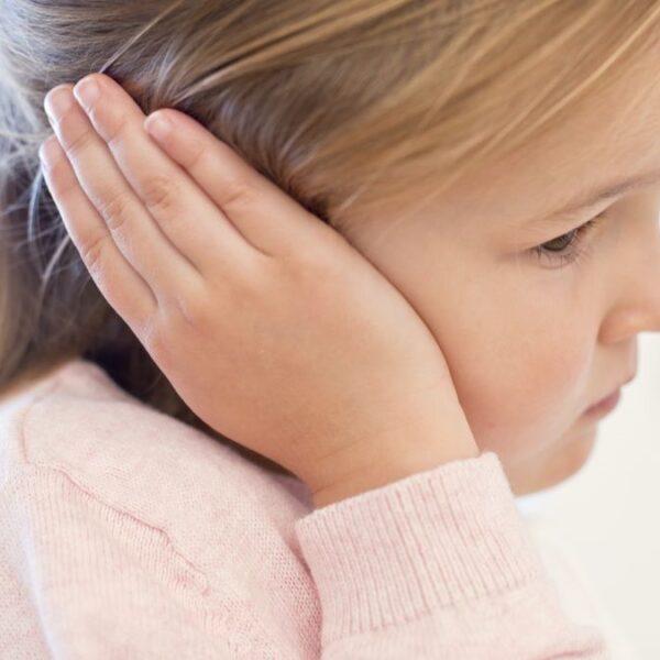 Little girl covering her ear