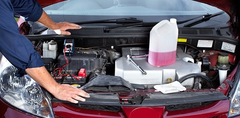 Man leaning on car whilst working under the hood