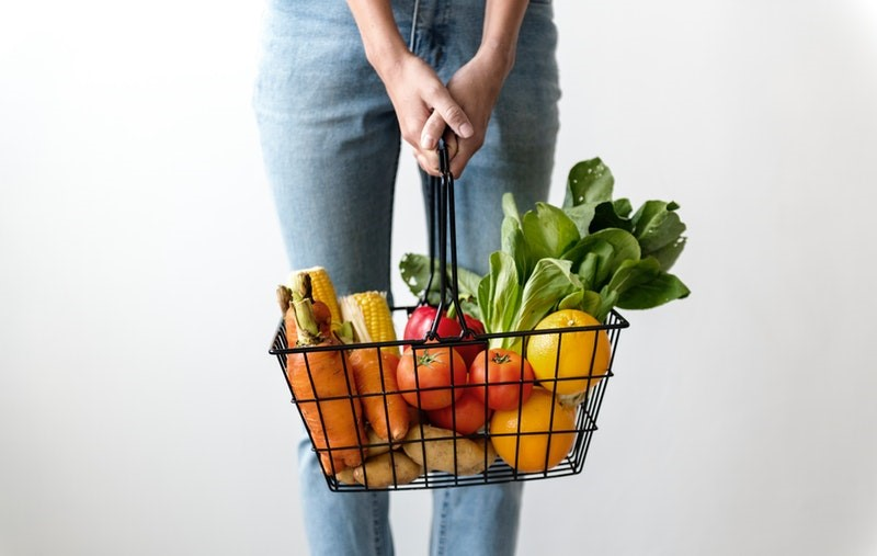 Person holding a basket of vegetables