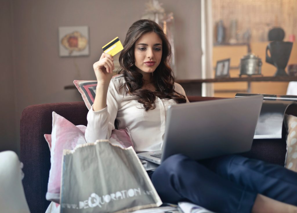 Woman holding card whilst using laptop